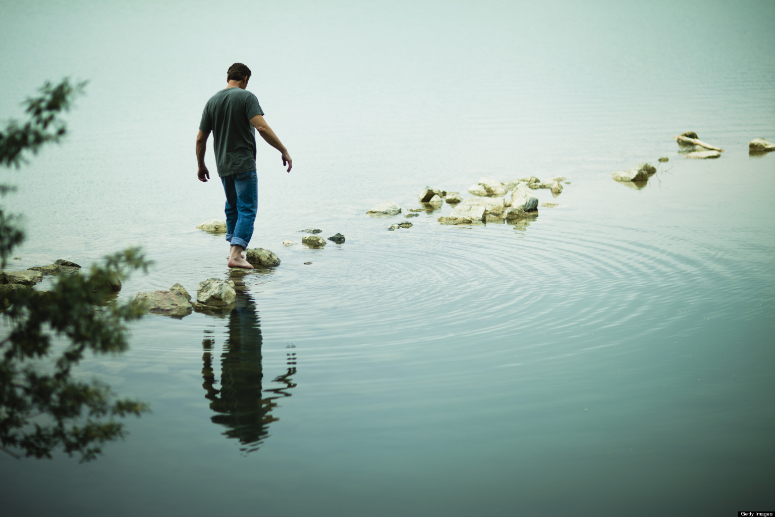 A man walking barefoot across stepping stones away from the shore of a lake.